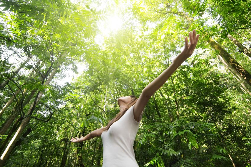 6669255 - young woman arms raised enjoying the fresh air in green forest